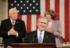 President Bush with Vice President Cheney and Speaker Pelosi standing  behind him. Click here for larger image.